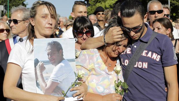 Laurence, centre, and Kevin, right, wife and son of Herve Cornara, who was beheaded in an attack near Lyons (AP)