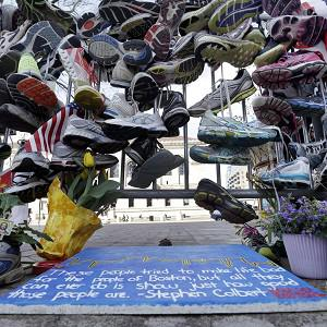 Running shoes hang on a fence at a makeshift memorial near the Boston Marathon finish line (AP Photo)