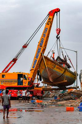 A crane lifts a boat from the shore ahead of the cyclone. Photo: Indranil Mukherjee/AFP via Getty Images