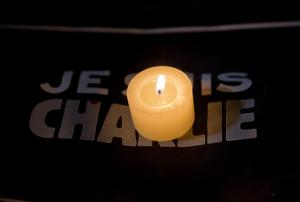 A candle burns beside a sign reading Je suis Charlie.
