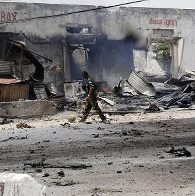 A Somali soldier walks near a destroyed building after a car bomb exploded near Mogadishu international airport (AP)