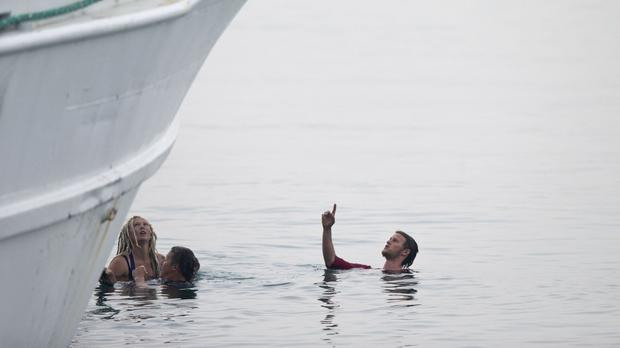 Activists in the sea try to block the deportation of Pakistani migrants on board a ferry set to sail for Turkey, in the port of Mytilini on the Greek island of Lesbos (AP)