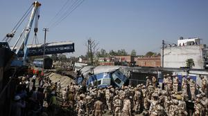 Rescue workers gather at the site of the train accident in the northern Indian state of Uttar Pradesh. (AP)