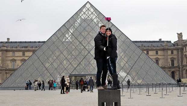 Tourists use a selfie stick in front of the Louvre Pyramide in Paris (Remy de la Mauviniere/AP)