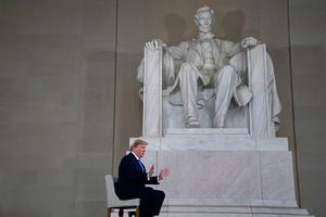 Split: President Donald Trump is dwarfed by a statue of Abraham Lincoln during a Fox News interview at the Lincoln Memorial in Washington. Photo: Evan Vucci/AP