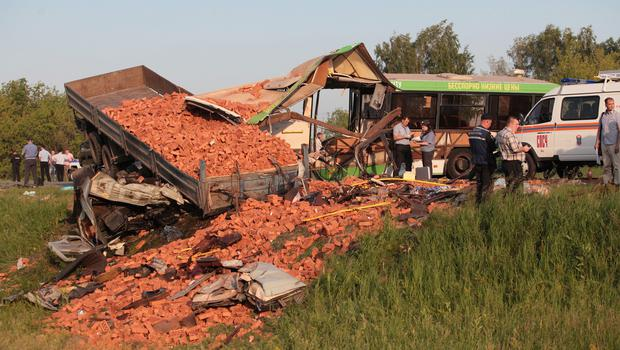 Police investigators work at a crash site of a bus and a truck on a highway near the Siberian city of Omsk. (AP)