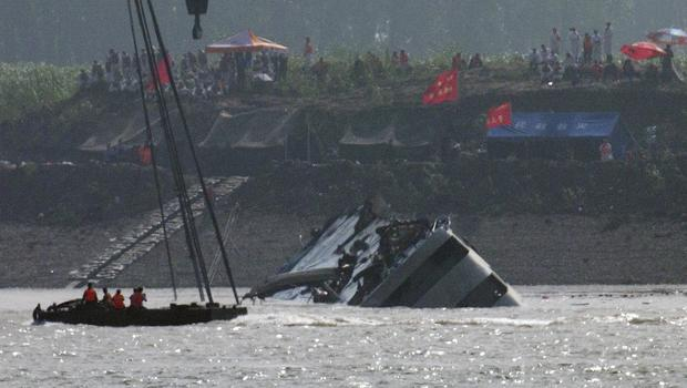 Rescuers on a boat watch a capsized ship being righted by cranes on the Yangtze River in Jianli county of southern Chinas Hubei province (AP)