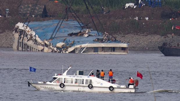 Rescuers on a boat watch the capsized ship Eastern Star being lifted by cranes on the Yangtze River. (AP)
