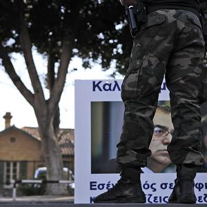 A riot police stands in front of a protestor with a banner display the image of the head of Cyprus central bank Panicos Dimitriades (AP Photo)
