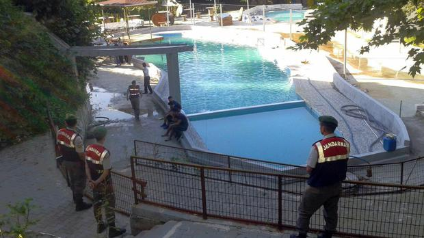 Paramilitary police officers investigate after five people were caught up in an electrical current in a pool at a park in the town of Akyazi, in Sakarya province, Turkey (IHA)