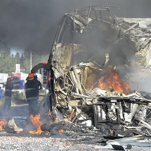 Firefighters put out the fire of a wrecked bus that collided head on with a truck near San Martin, Argentina (AP)