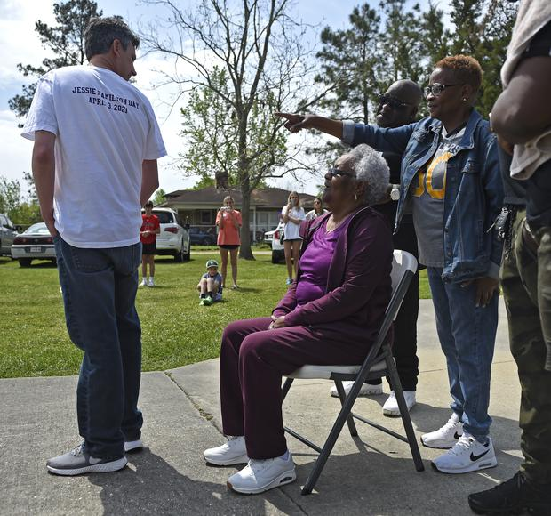Andrew Fusaiotti, left, turns around to show Jessie Hamilton, seated, the back of his shirt as Ms Hamilton's daughter, Yonetta Tircuit, right, points as LSU FIJI graduates gather to surprise their former house kitchen staff member to pay off her mortgage and celebrate Jessie Hamilton Day in Baker, Louisiana (Hilary Scheinuk/The Advocate via AP)