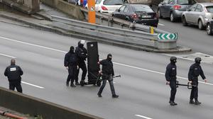Hooded police officers walk on the closed ringroad that circles Paris near a hostage-taking situation at a kosher market (AP)