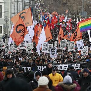 Opponents of Vladimir Putin carry posters of imprisoned protesters during a rally in Moscow (AP Photo/Alexander Zemlianichenko)