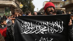 Anti-Assad protesters hold the Jabhat al-Nusra flag, as they shout slogans during a demonstration, at Kafranbel town, in Idlib province, northern Syria (AP)