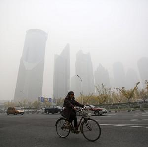 A woman rides a bike in the smog in Shanghai, China (AP)