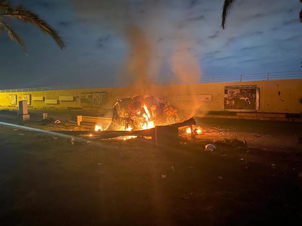 A burning vehicle at the airport after the air strike (Iraqi Prime Minister Press Office/AP)