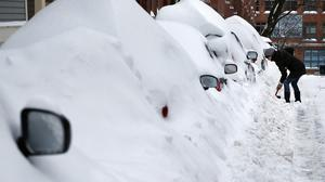 A resident tries to reach her car in Boston's Charlestown area after a blizzard dumped about 2ft of snow in the city. (AP)