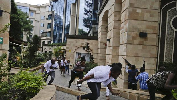 Civilians flee as security forces aim their weapons at the buildings of the hotel complex in Nairobi (Khalil Senosi/AP)