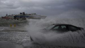 A car drives through seawater from crashing waves during bad weather at the port of Rafina, east of Athens (Thanassis Stavrakis/AP)