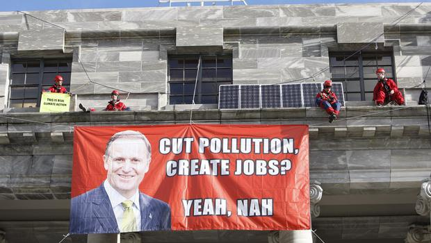 Greenpeace protesters on a ledge above the main entrance of New Zealand's parliament (AP)