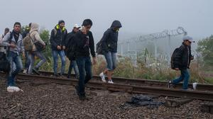People walk at the railway track and cross the border line between Serbia and Hungary in Roszke, southern Hungary (AP)