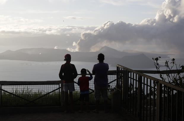 People watch from Tagaytay as the Taal volcano continues to spew ash (AP)