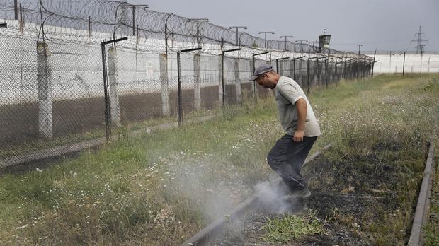 A prisoner tramples smouldering grass in a high-security facility after shelling in Donetsk, during which more than 100 prisoners apparently fled a high-security jail (AP)
