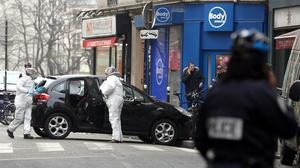 Forensic experts examine the car believed to have been used as the escape vehicle by gunmen who attacked the French satirical newspaper Charlie Hebdo's office, in Paris (AP)