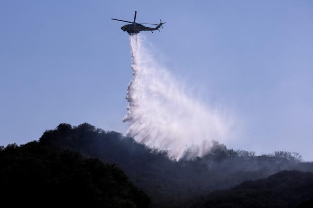 A helicopter makes a water drop to put out hotspots in a wildfire in Topanga, west of Los Angeles (Ringo HW Chiu/AP)