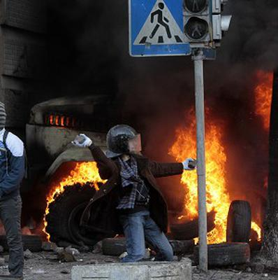 An anti-government protester throws a stone during clashes with riot police outside Ukraine's parliament in Kiev (AP)