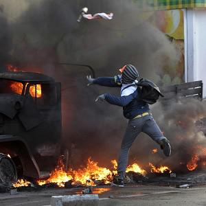 An anti-government protester throws a Molotov cocktail during clashes with riot police outside Ukraine's parliament in Kiev (AP)