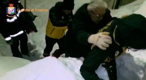 A man is helped out of the Hotel Rigopiano. Photo:  AFP/Guardia di Finanza