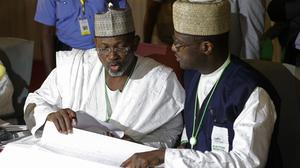 Independent National Electoral Commission chairman Attahiru Jega, left, views election results at the coalition centre in Abuja, Nigeria (AP)
