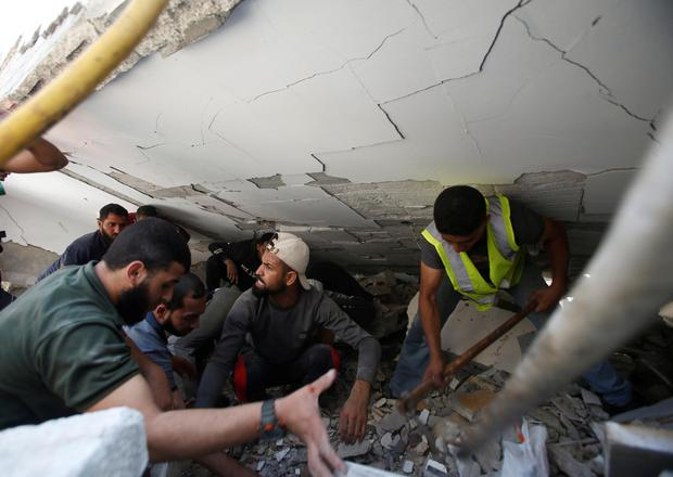Rescue workers search for victims amid rubble at the site of Israeli air strikes, in Gaza City on Sunday morning. Photo: REUTERS/Mohammed Salem.