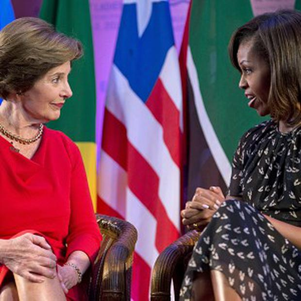 US first lady Michelle Obama and former US first lady Laura Bush participate in a summit hosted by the George W Bush Institute in Dar es Salaam (AP)