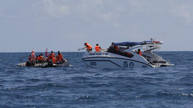 Thai rescue divers and a police boat during a search mission (AP Photo/Vincent Thian)