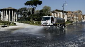 A street cleaner sprays disinfectant in central Rome (Cecilia Fabiano/LaPresse/AP)