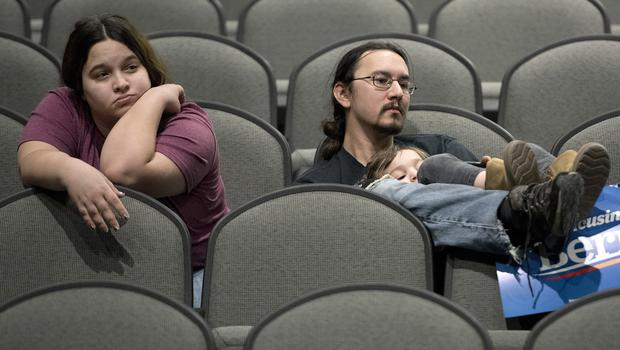 Jeff Lopez holds his son, Tristan, four, as they and Jeff's wife, Jessika, sit in an area for Bernie Sanders supporters (Tim Hynds/AP)