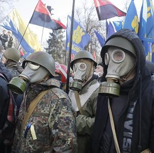 Anti-government protesters look on during clashes with riot police outside Ukraine's parliament in Kiev (AP)