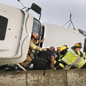 Firefighters assist driver Marco Corr from the cab of his overturned truck after a tornado caused extensive damage in Oklahoma (AP)