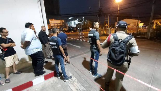 Police and bystanders stand near the scene of a shooting at the Terminal 21 mall, in Korat, Thailand, Saturday, Feb. 8, 2020. Police in northeastern Thailand said a soldier shot multiple people on Saturday, killing more than 10, and was holed up at a popular shopping mall. (AP Photo)