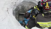 Italian firefighters extracting a boy alive from under snow and debris in Rigopiano (Italian Firefighters/Ansa/AP)
