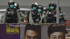 Riot police stand guard at Central during the second day of debate on a contentious bill that would criminalize insulting or abusing the Chinese national anthem, in Hong Kong (Vincent Yu/AP)