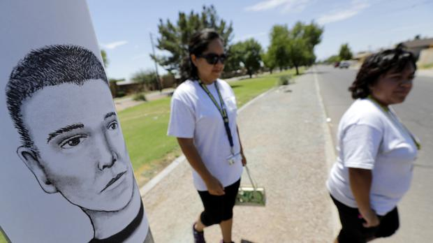 Neighbourhood patrol officers walk the streets of Maryvale in Phoenix to hand out an artist's sketch of a suspected serial killer (AP)