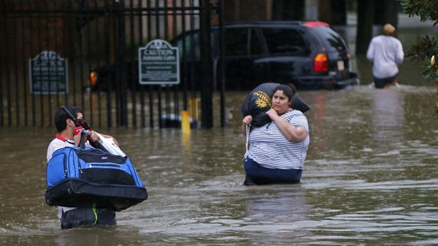 People wade through floodwaters from heavy rains in Baton Rouge (AP)