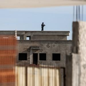 A Tunisian anti-terrorist police officer stands on a roof near a house where suspected Islamist militants were hidden in Raoued, near Tunis (AP Photo/Aimen Zine)