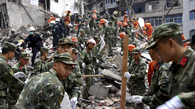 Rescuers clear the debris to search for victims on the site of collapsed residential buildings in Wenzhou (AP)