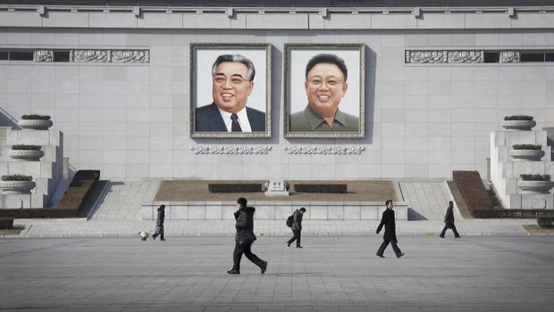 People walk past portraits of late North Korean leaders Kim Il Sung and Kim Jong Il in Pyongyang (AP)