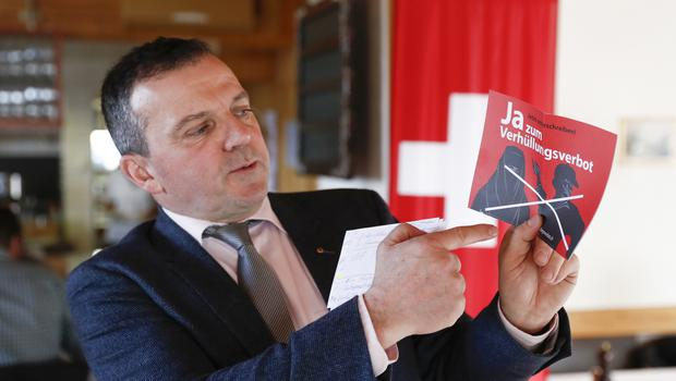 """Walter Wobmann displays a leaflet reading """"Yes to the ban on veiling'' at a meeting of the Swiss People's Party SVP in Dornach, Switzerland (Peter Klaunzer/Keystone via AP)"""